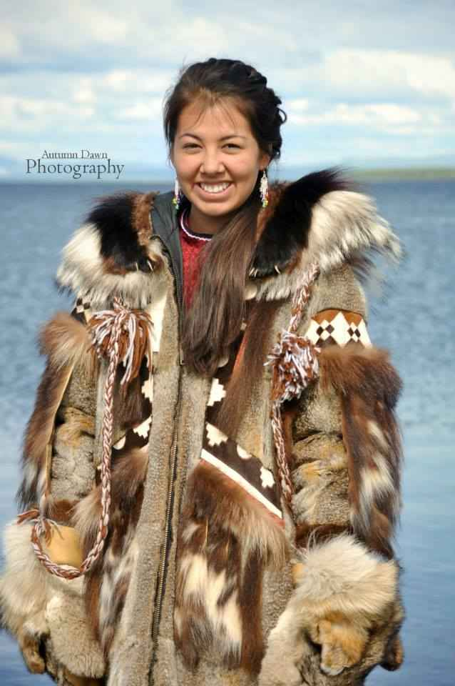 A young woman dressed in traditional Alaska Native clothing and furs stands against a body of water.