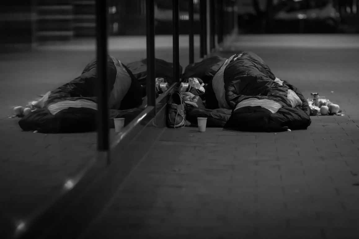 A black and white photo of a man sleeping on the street.