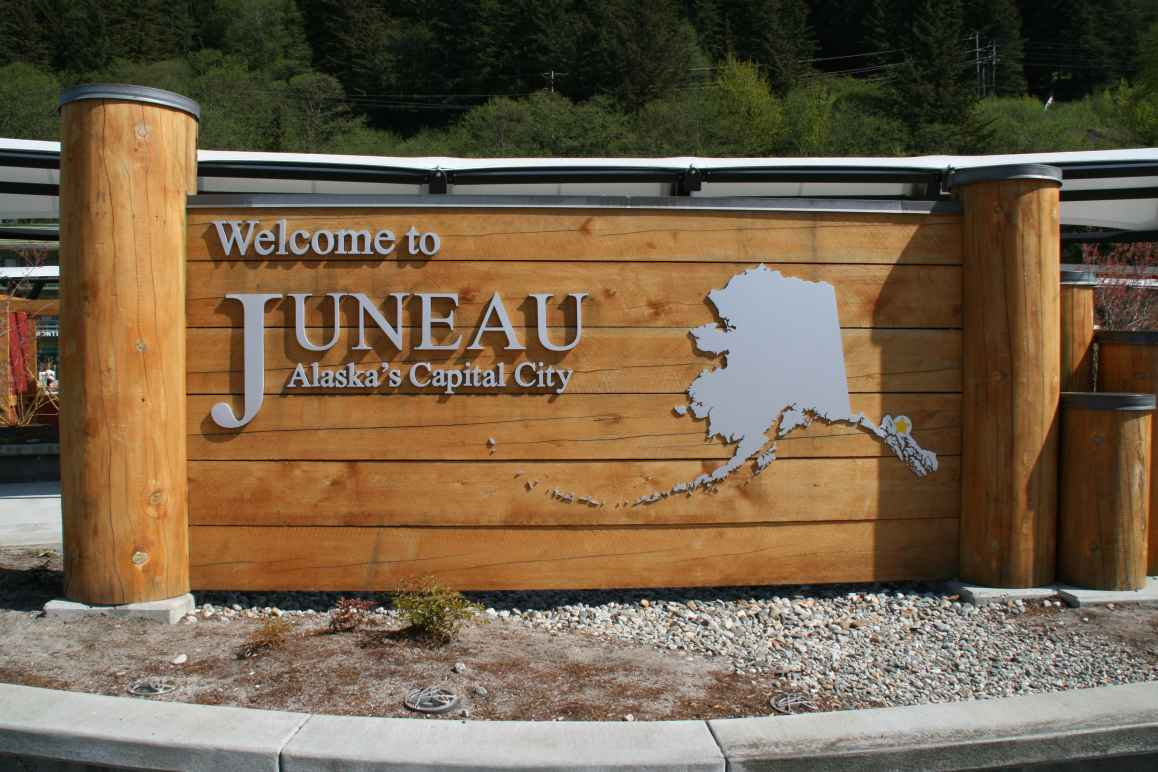 "A wooden sign says ""Welcome to Juneau - Alaska's Capital City"" next to a map of Alaska"