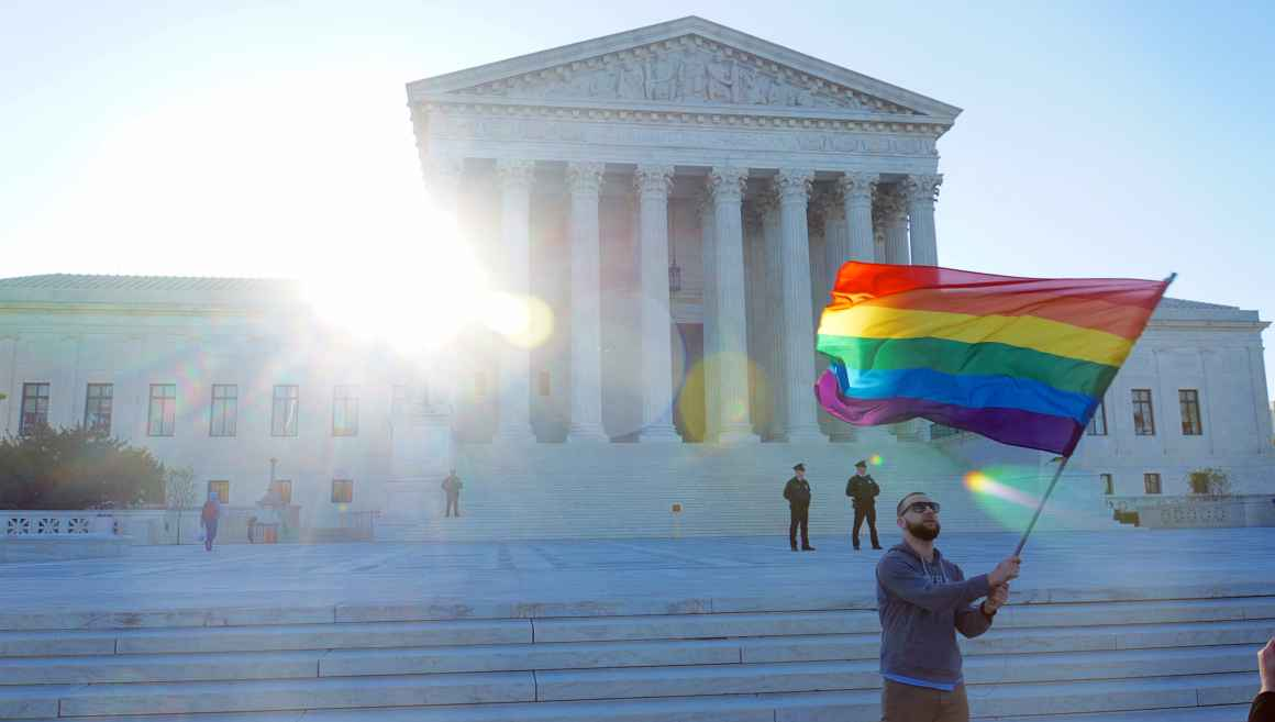 A man waves a rainbow flag in front of the steps of the Supreme Court.