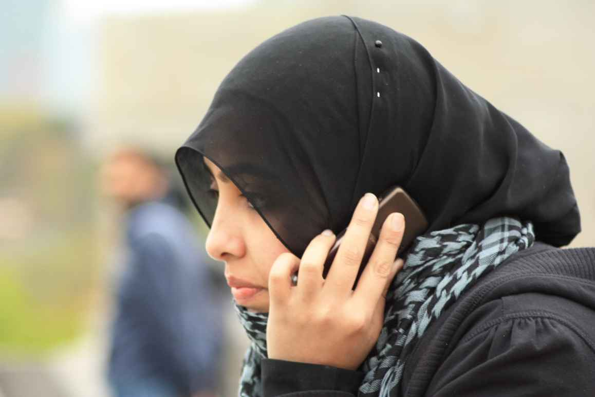 A woman in a black hijab used a smartphone