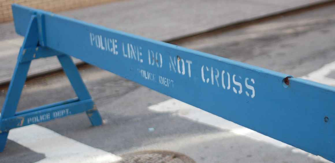 "A blue barrier saying ""Police Line Do Not Cross"""