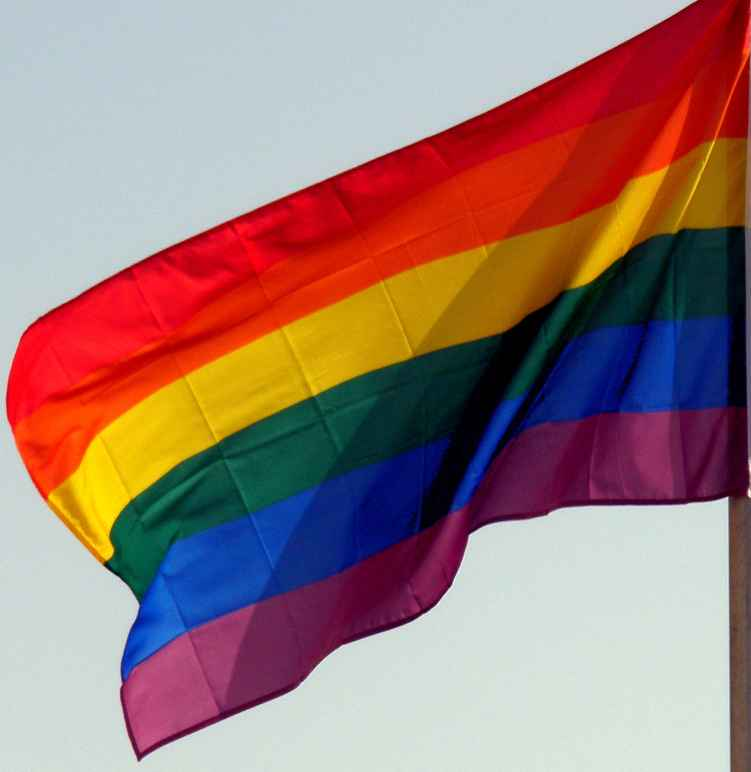 A rainbow flag against the backdrop of a blue sky.