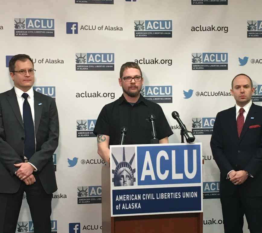 ACLU staff attorney Eric Glatt, plaintiff Lance Hunt, and executive director Joshua Decker stand in front of a podium