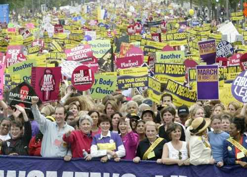 People hold up signs and slogans at a rally in support of reproductive rights.