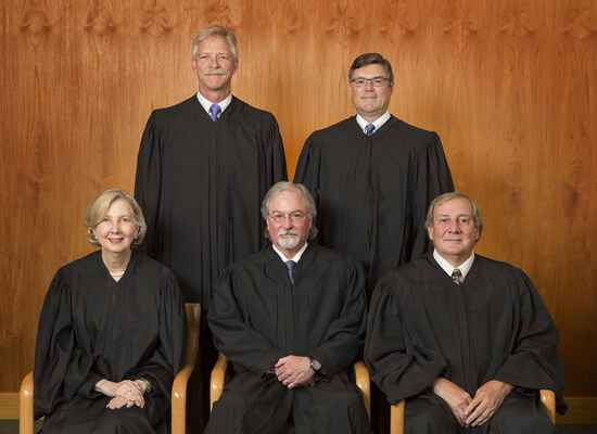 The Alaska Supreme Court justices (four men and one one woman) sit on a bench, all wearing black judicial robes.