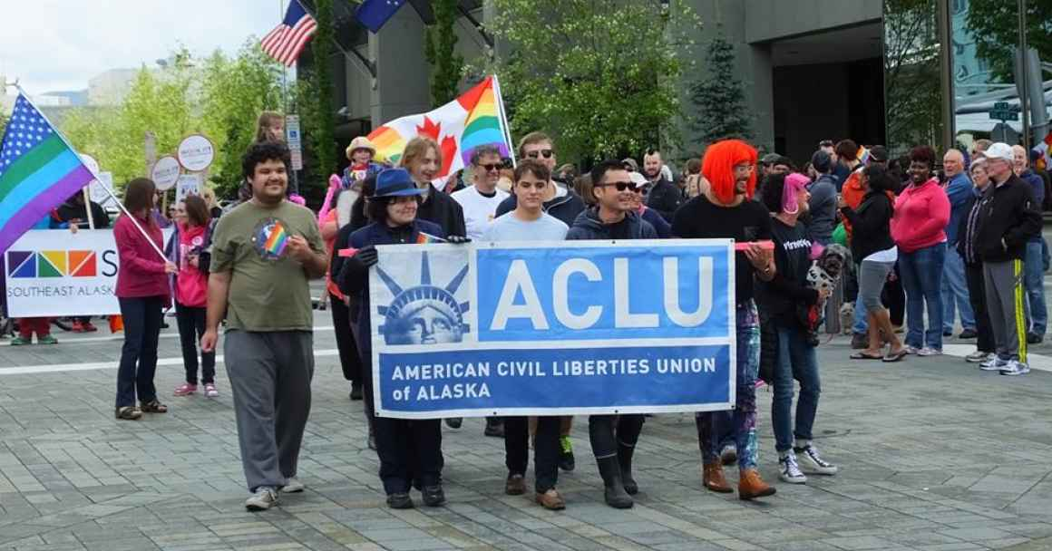 A group of people marching behind the ACLU banner.